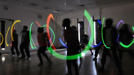 Dancers with glow tubes at the Rave Fit class at the Copperbox arena