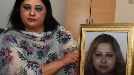 Murder victim Sannah Javed's Mother Qasira Ahmad holds a portrait of her daughter who was killed by
