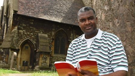 Chigor Chike with his new book in the grounds of Emmanuel Church