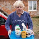 Boris Johnson brings tea for the press to drink outside his house in Thame.