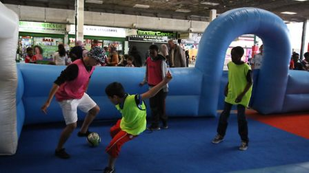 Children take part in a football match at the Queen's Market community games