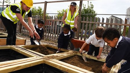 Children planting in the new temporary community garden in the Queen Elizabeth Olympic Park