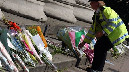 A Police officer lays flowers near the scene of the bus explosion in Tavistock Square. Picture: Stev
