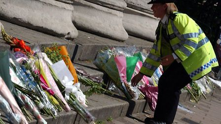 A police officer laying flowers near the scene of the bus explosion in Tavistock Square. Picture: St