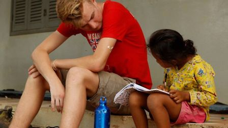 Henry Allinson helping a student to read in Cambodia