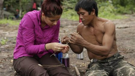 One of the jungle guides shows Ellen Johnson how to weave a ring