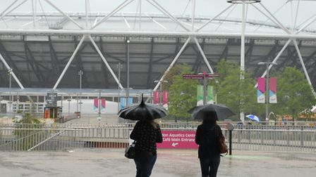 Visitors to Queen Elizabeth Olympic Park shore up against the rain