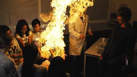 Professor Brian Cox looks on as young students experiment with chemica reactions