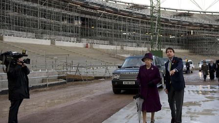 Britain's Queen Elizabeth II is shown a stretch of the 100m track at the main Olympic stadium constr