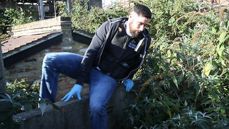 Pc Jimmy Atkins climbing up from an abandoned house off Roden Street, Ilford.