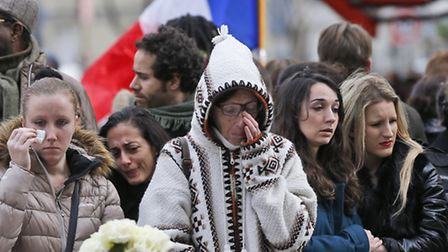 People pay respect to the victims in front of the Carillon Restaurant in Paris where terrorists atta