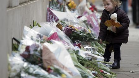 Ines Grissett, 2, lays flowers outside of the French Embassy in London after terror attacks killed a