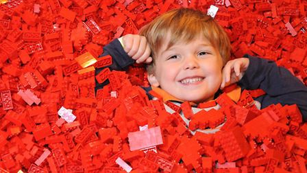 A young boy is covered in red Lego bricks at last year's Brick exhibition