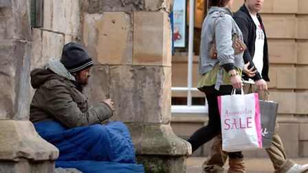 Shoppers pass by a homeless man in a city centre. Picture Anna Gowthorpe/PA Archive/PA Images