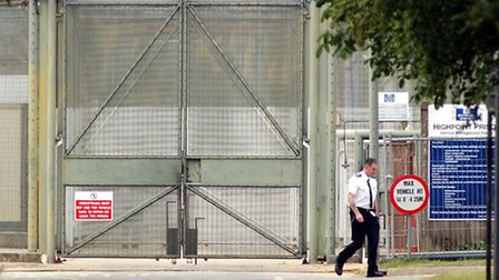 A Prison Officer at walking past the gates of HMP Highpoint Prison in Suffolk