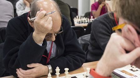 A chess player in deep concentration as he plans his next move at a chess tournament in London. Phot