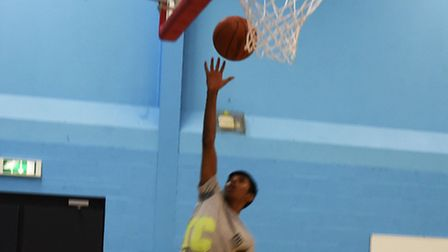 A young player shoots a hoop during a training session