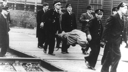A victim on a stretcher is carried away from the station after the 1953 Stratford Tube crash