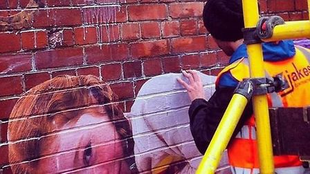 Artist Bifido creating part of the wall mural at Forest Gate station. Picture: Bifidoart/Instragram