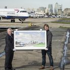 Artist Gerry Buxton holds his artwork with London City Airport boss DEclan Collier as a plane taxis