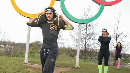 Iain Burns walks past the Olympic rings with sandbag wights on either shoulder