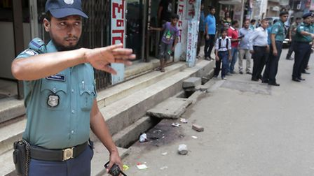 A Bangladeshi policeman stands guard at the spot where three motorcycle-riding assailants hacked sec