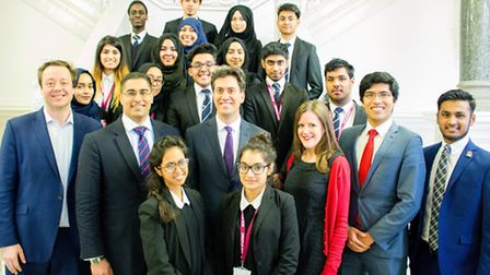 Ed Miliband, centre, with staff and students