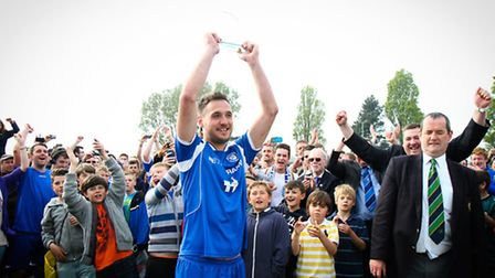 Skipper Dan Glesson lifts the trophy aloft as Lowestoft Town FC celebrations start, with chairman Ga