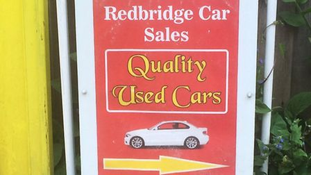 A sign for the dealership, which is trading without planning permission on the site behind hoouses o