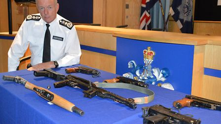 Met Police commissioner Sir Bernard Hogan-Howe and recovered firearms