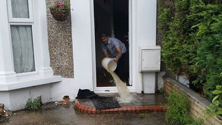 A resident clearing water out from their flooded home in Spencer Road, Seven Kings