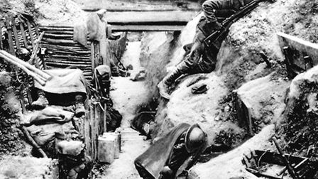 A British Grenadier Guardsman keeping watch on No Man's Land as his comrades sleep in a captured Ger