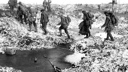 British soldiers negotiating a shell-cratered, winter landscape along the River Somme in late 1916.