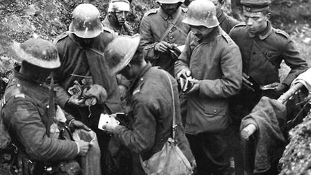 British troops sorting through the belongings of German prisoners in a trench, with articles being p
