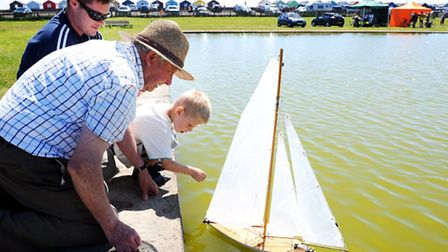 Touching the Tide celebration day at Southwold.Reece Fosker sailing a model boat on the boating lake