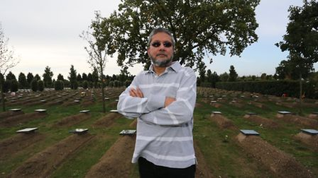 Mohamed Omer founding member of the Gardens of Peace cemetery with the graves behind him.