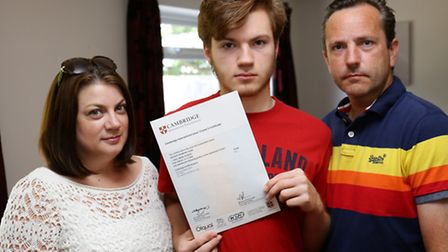 George Goss holds his IGCSE certificate with mum Gill and dad Daniel
