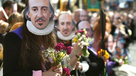 Members of the public wear William Shakespeare masks during the parade marking 400 years since the d