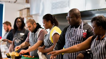 UEL student Maud Hesse and care leaver Simeon Sargeant prepare vegetables (foreground of photo). Pic