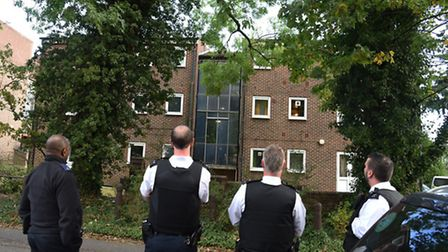 Police try to talk a man down from the roof of a block of flats on Bunces Lane Woodford Green