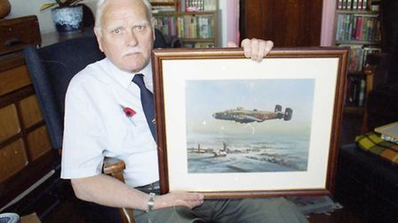 Former RAF navigator Douglas Smallbone with a painting of his aircraft.