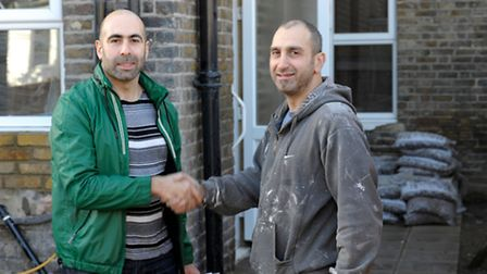 Left, Richard Blanco, of the National Landlords Association, shaking hands with his builder.