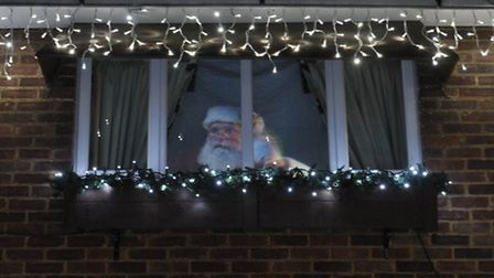 Santa appearing at the window of the house.