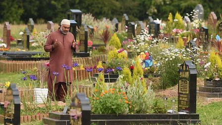 A man pays his respects at a grave in a Muslim section of a cemetery. Photo: Joe Giddens/PA Wire
