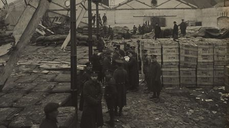Firemen and police pick over rubble in the Royal Victoria Dock.