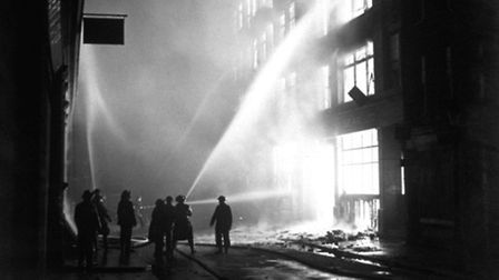 Fire-fighters put out a blazing building after an incendiary raid on the City of London during the B