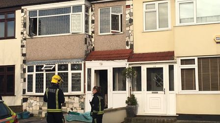A firefighter and police officer outside the property in Laburnum Avenue, Hornchurch, the scene of a
