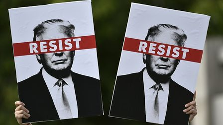 A protestor holds placards prior to the Scotland United Against Trump march through the streets of E