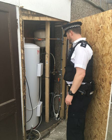 A Newham police officer discovers an outside boiler in use. Picture: Kat Hopps
