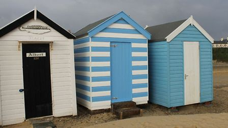 The beach hut Victoria (centre), which is on the market for £75,000